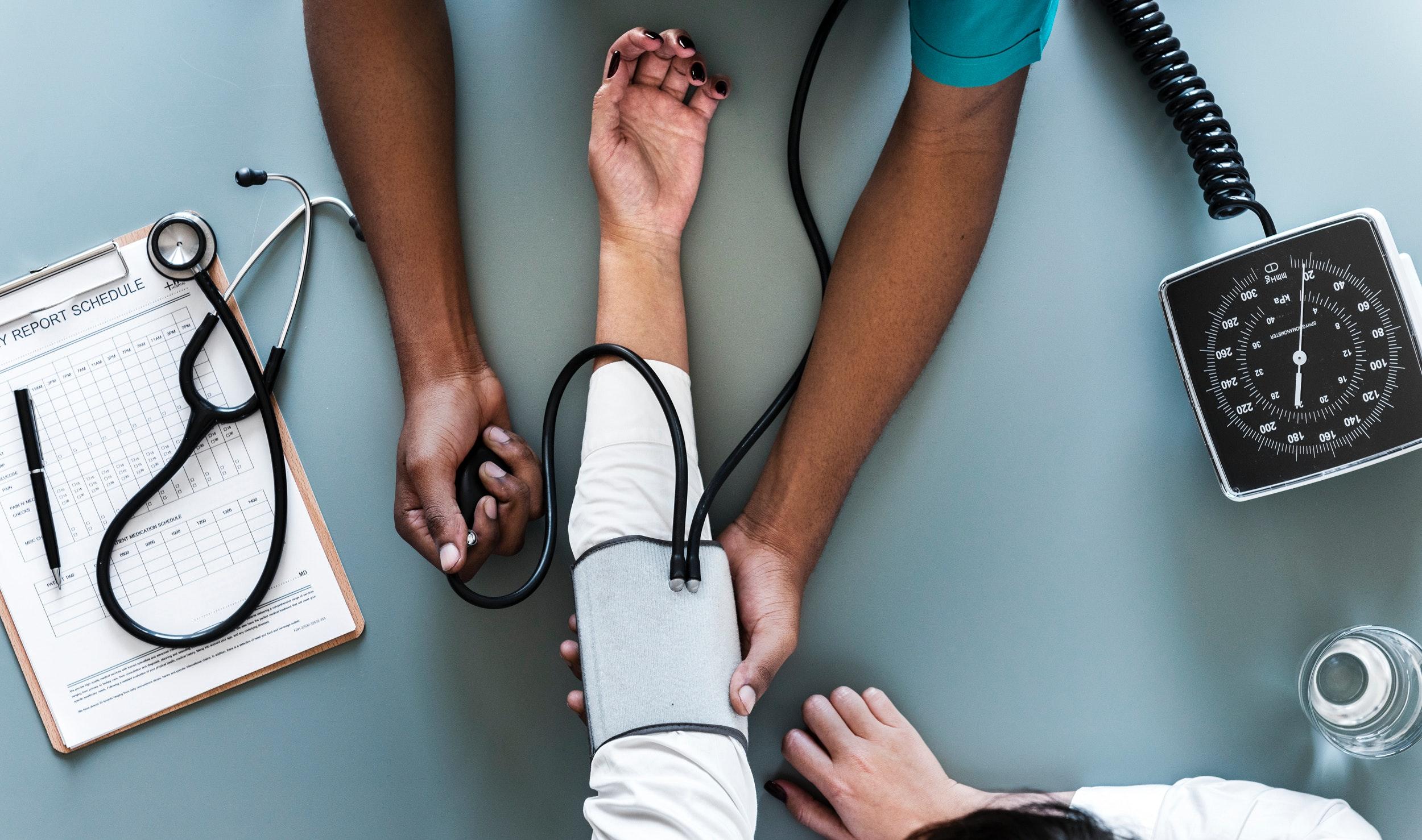 Läkare tar blodtryck på patient